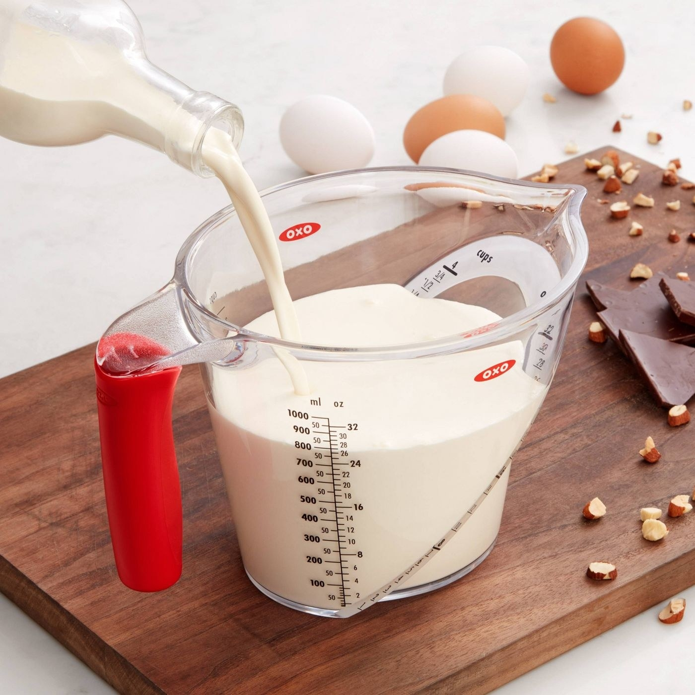 person pouring in milk into an angled oxo measuring cup