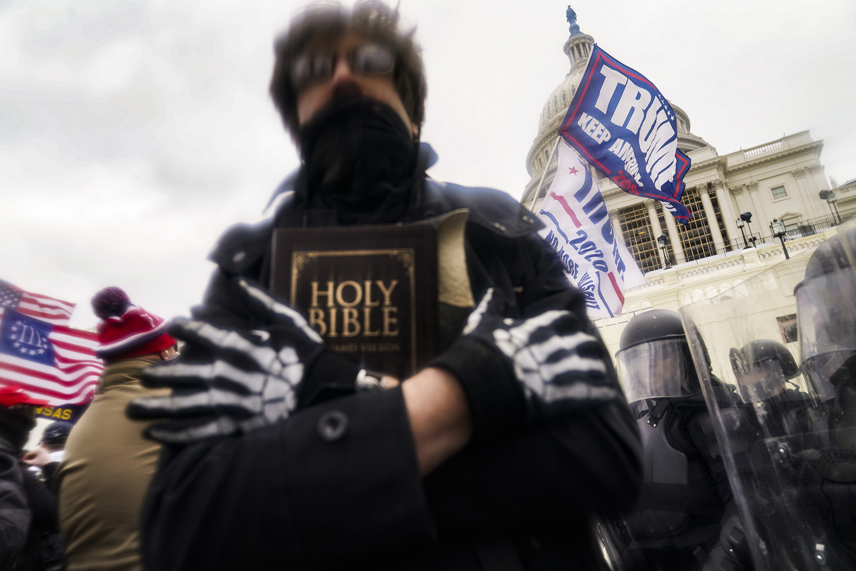 A man clutching a bible during a riot at the Capitol