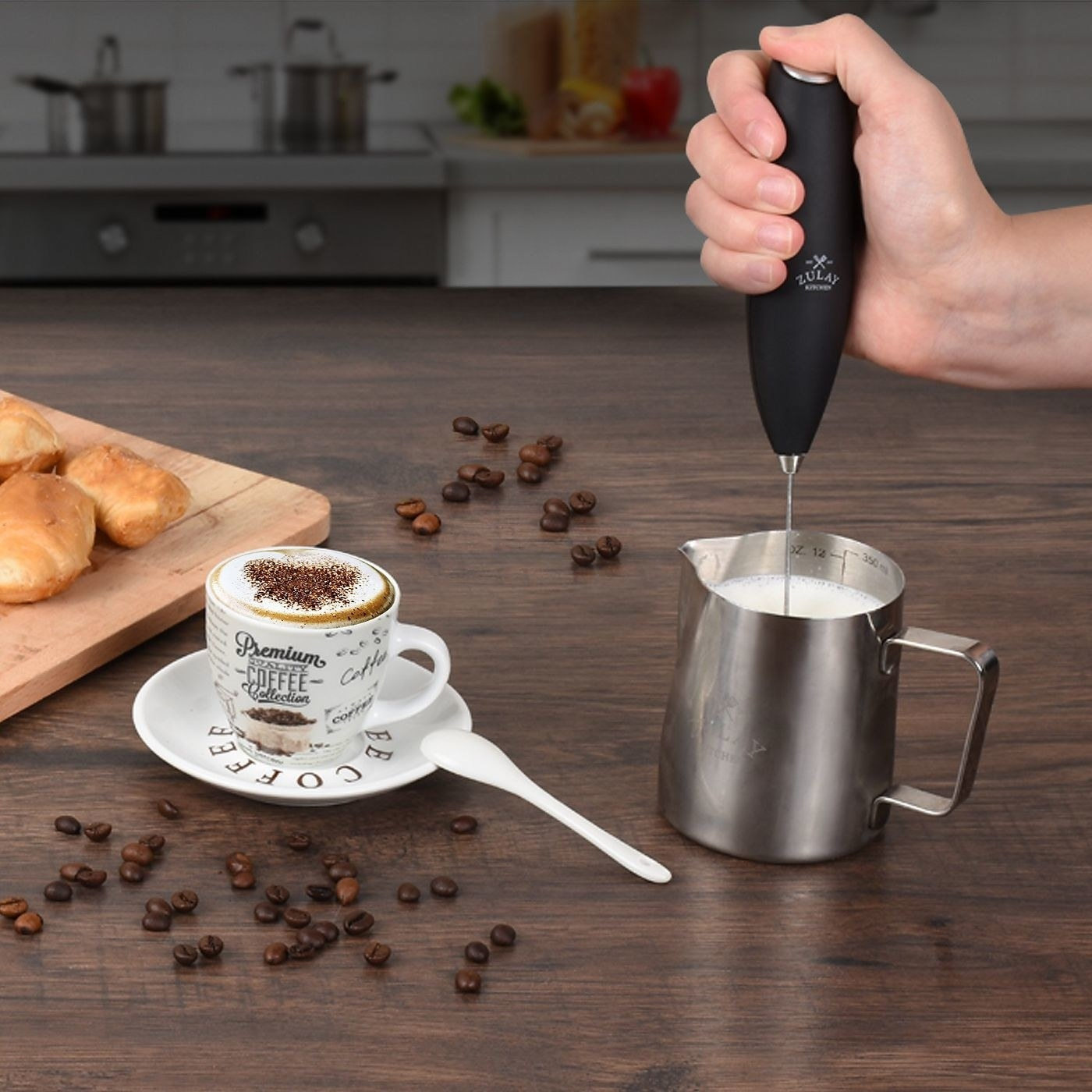 person using a milk frother in a stainless steel milk jar