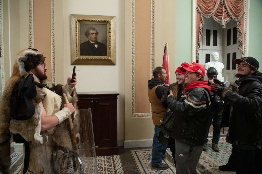 Rioters taking photos of each other inside of the Capitol after storming the building