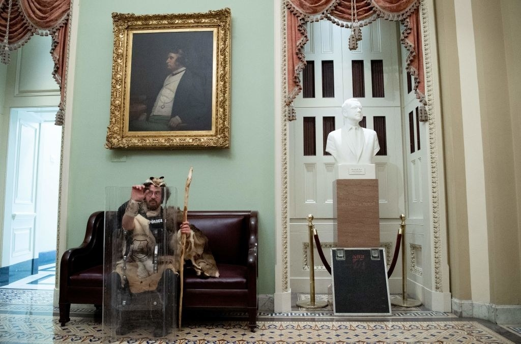 Rioter casually sitting on a couch next to a bust inside the Capitol after storming the building