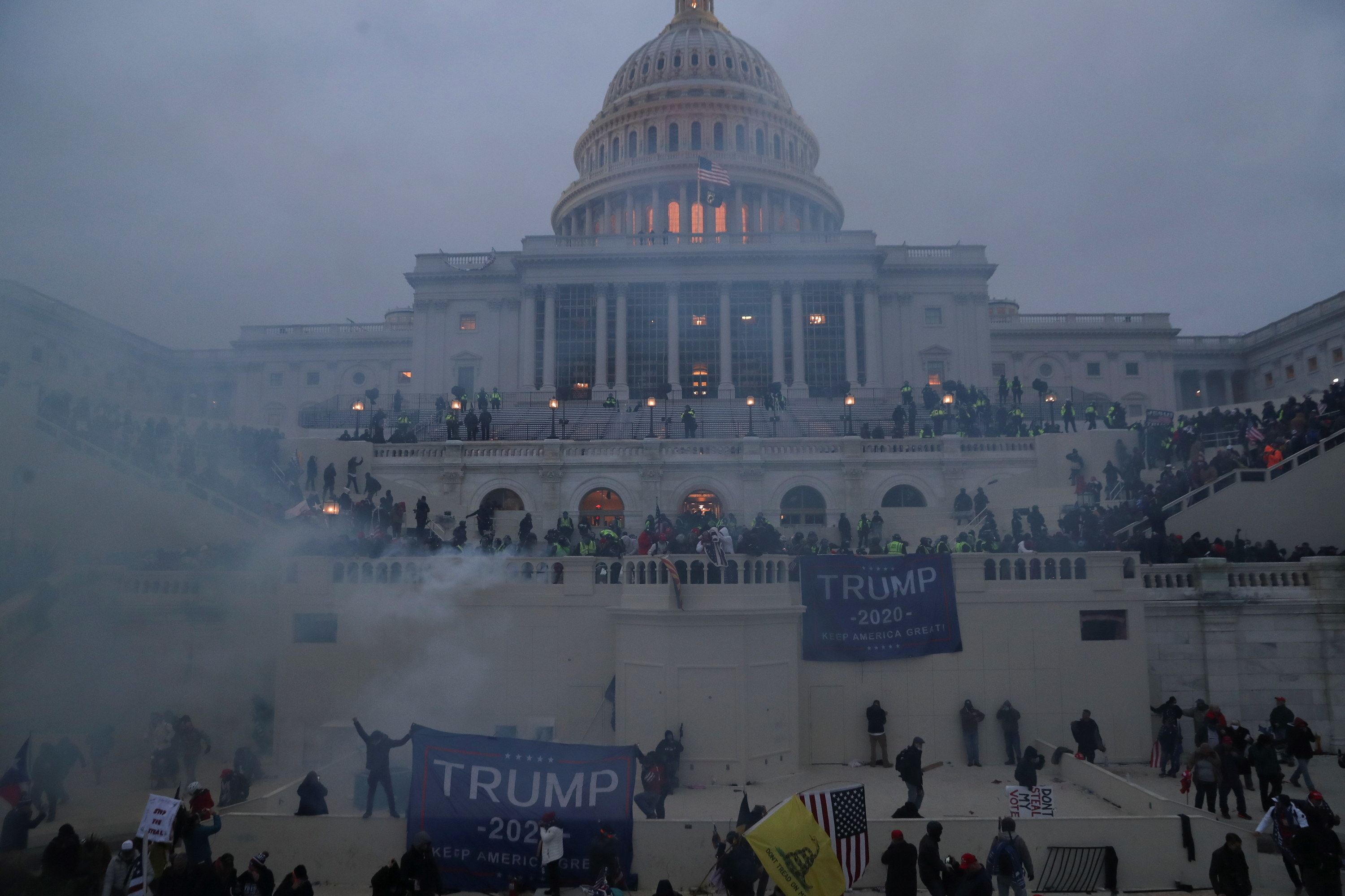 Trump supporters at the Capitol building while the sun sets.