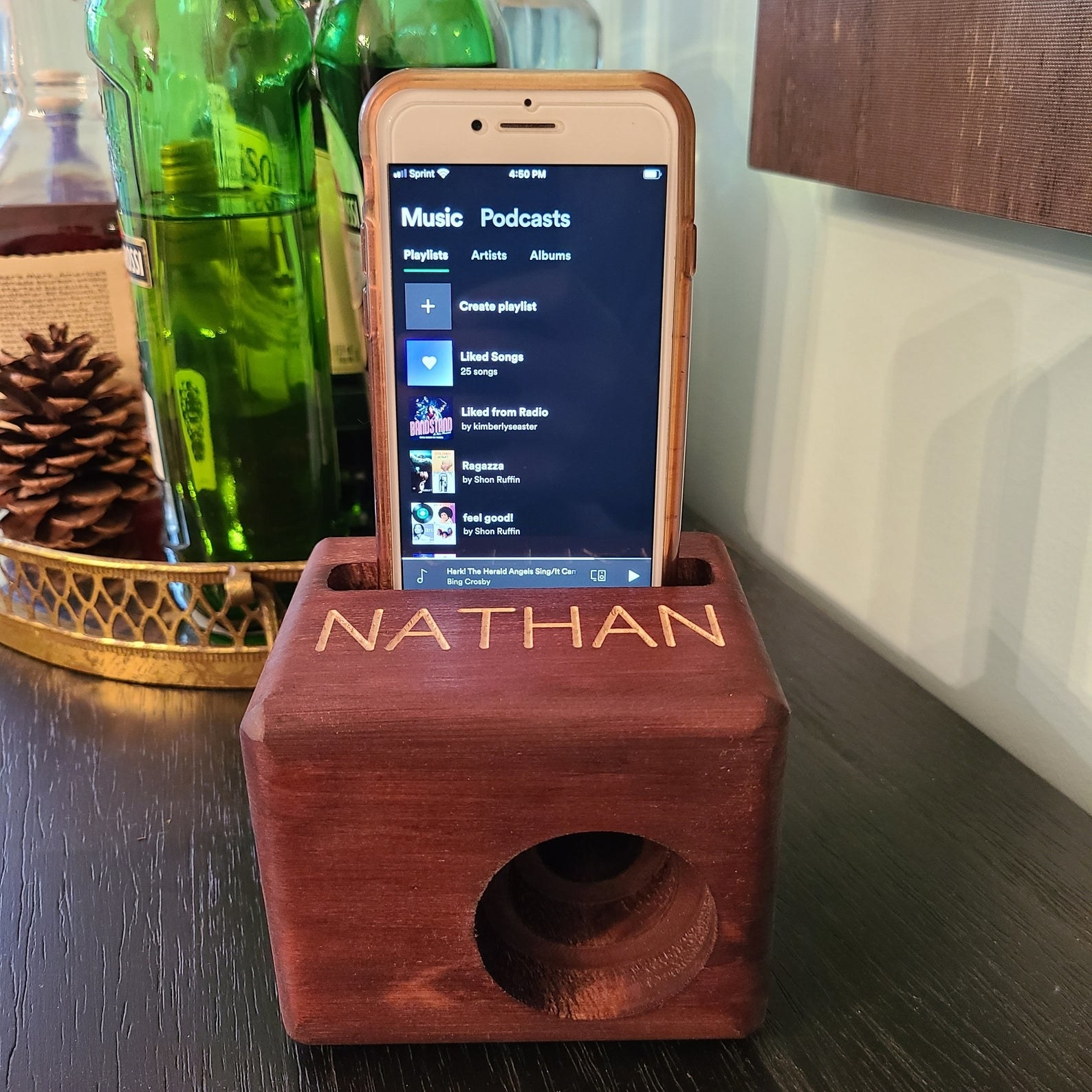 "The phone speaker with the name ""NATHAN"" on it, playing music from Spotify on an iPhone"