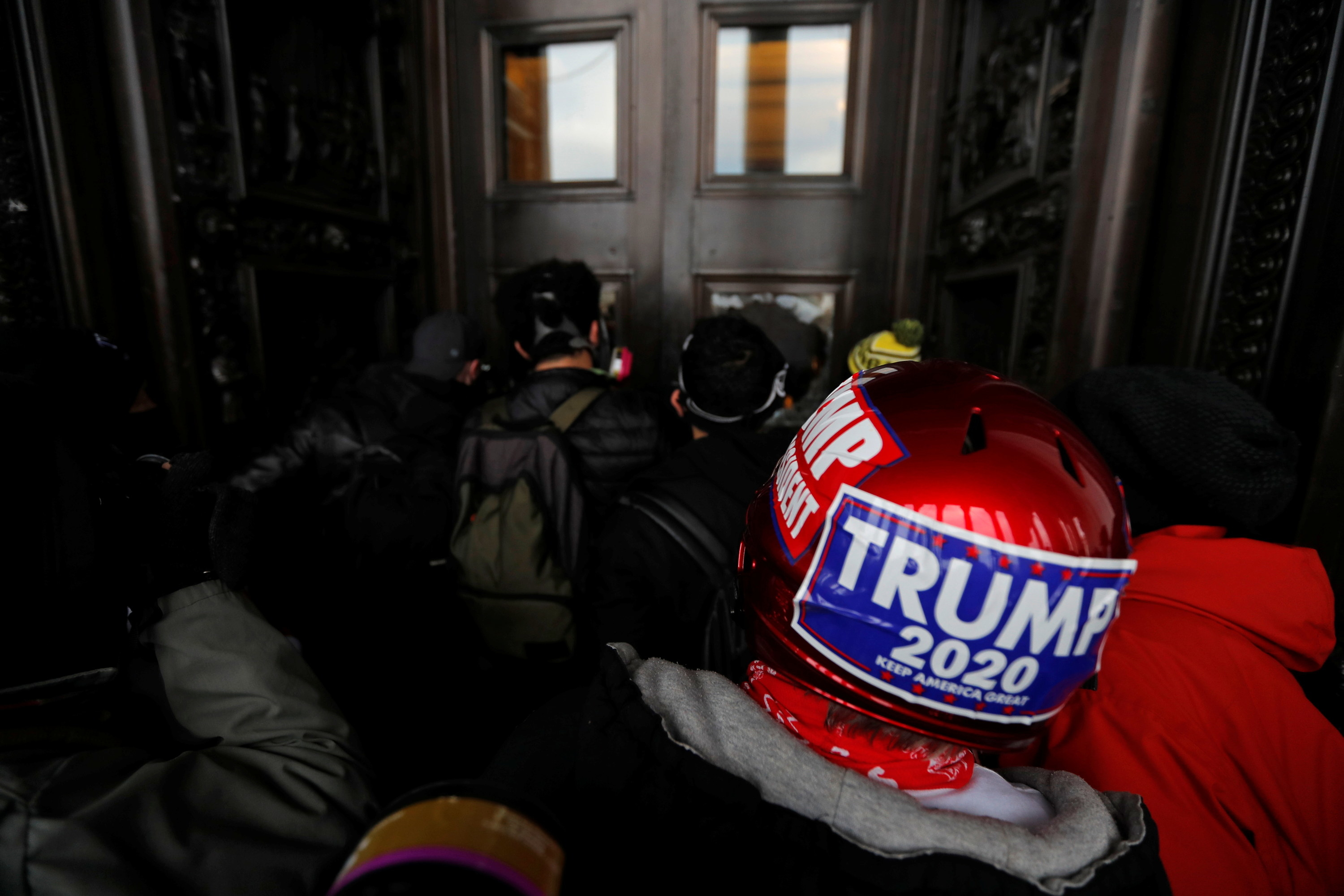Man in a trump helmet in the dark outside the Capitol