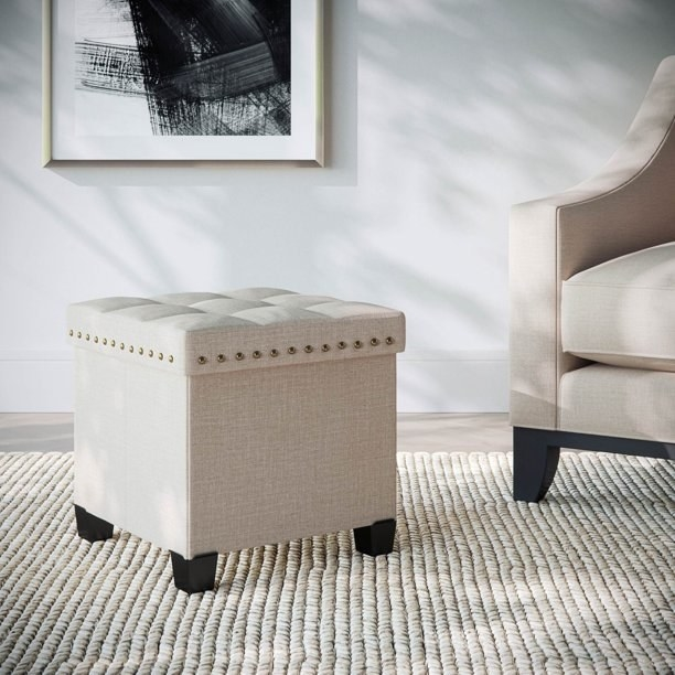 The ottoman, which is cube-shaped, and has tufting on top and nailhead trim around the top sodes