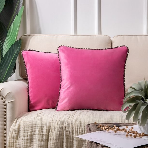 The pillows in pink, which are square and have some thin dark trim around the edges