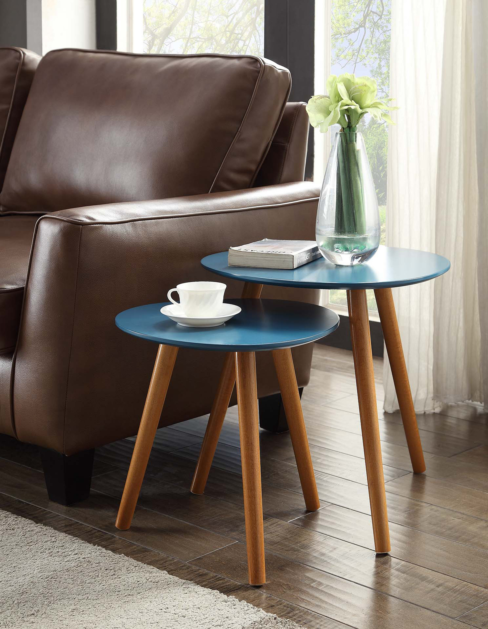 The set, which includes one small table that fits under a larger table, both with rounded tops and splayed legs, in blue, with natural wood colored legs