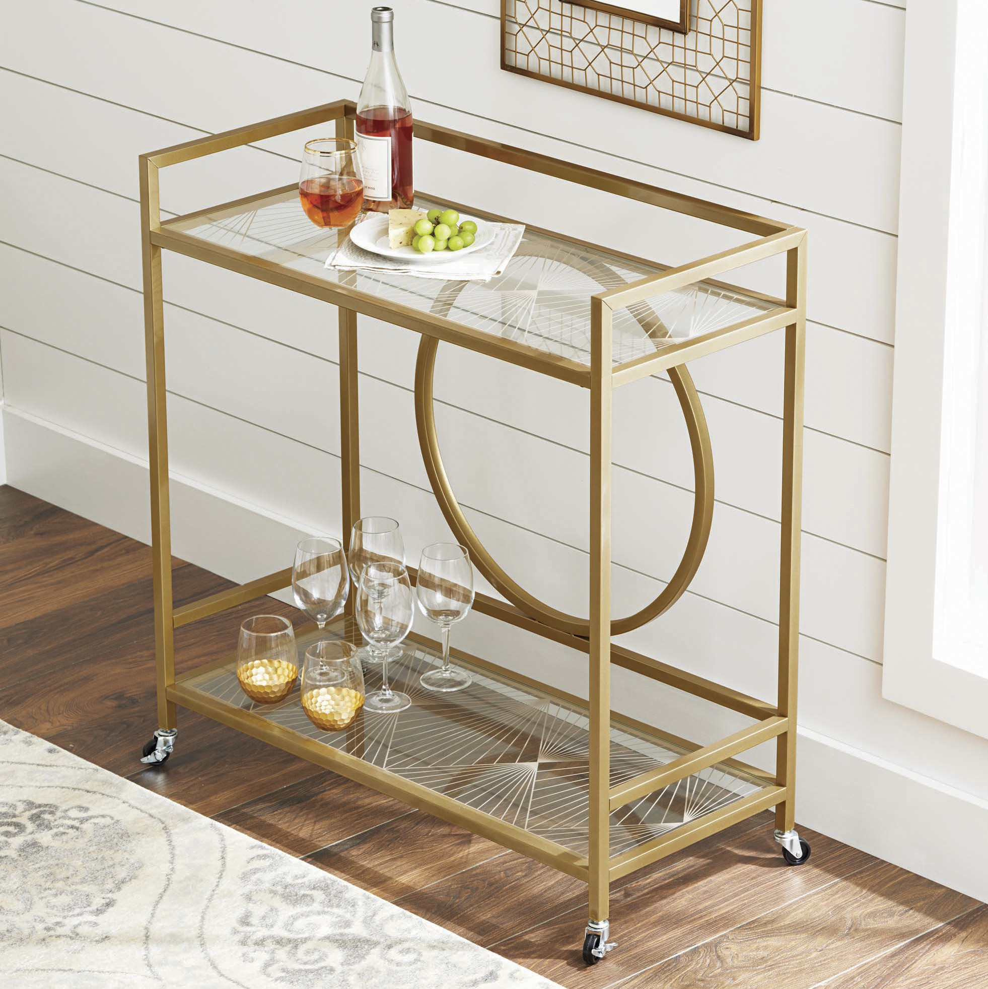 The bar cart, which has a gold finish frame, glass shelves on the top and bottom, and a circular design in the back area