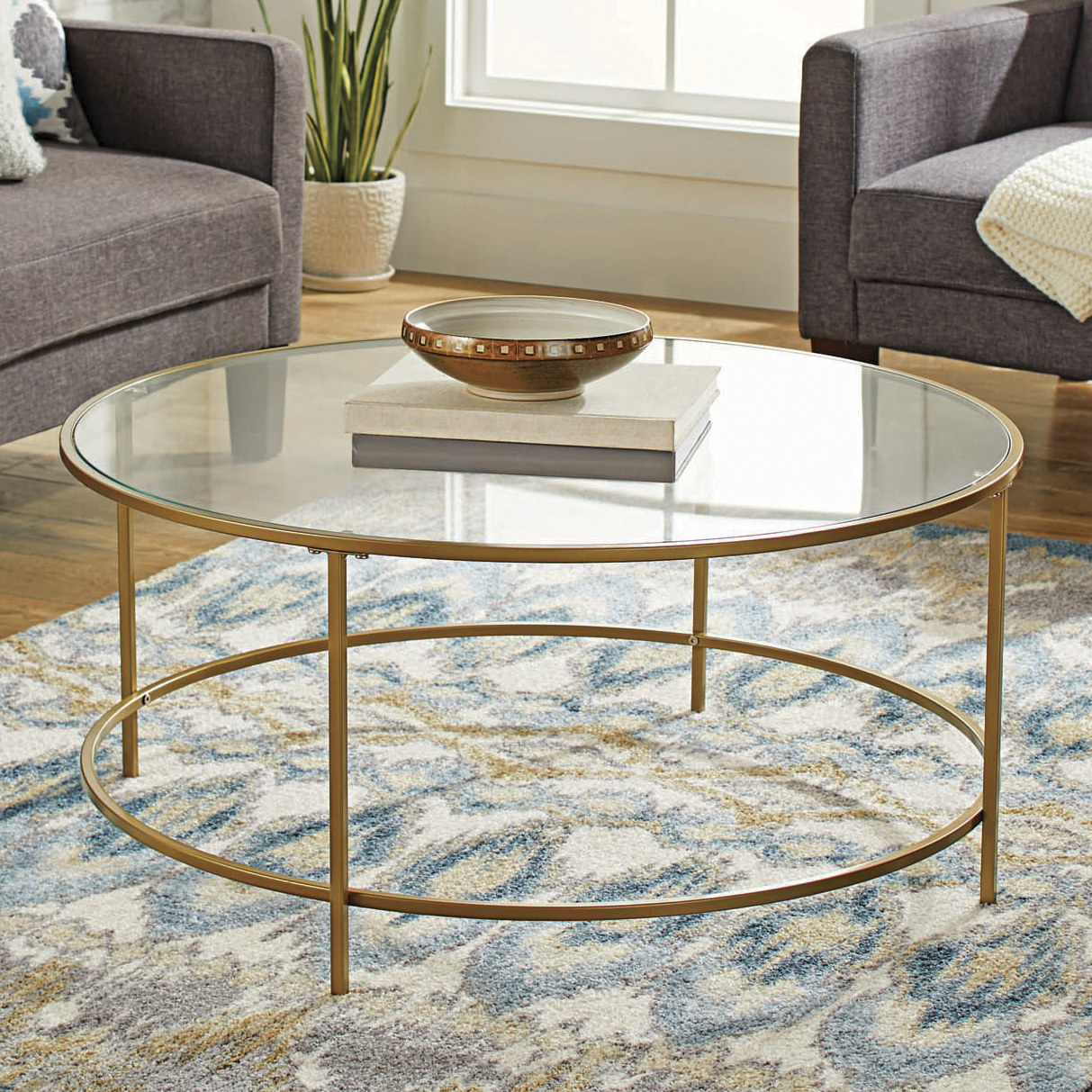 The table, which is circular, with a round, metal frame, four legs, and a circle of safety glass as the top