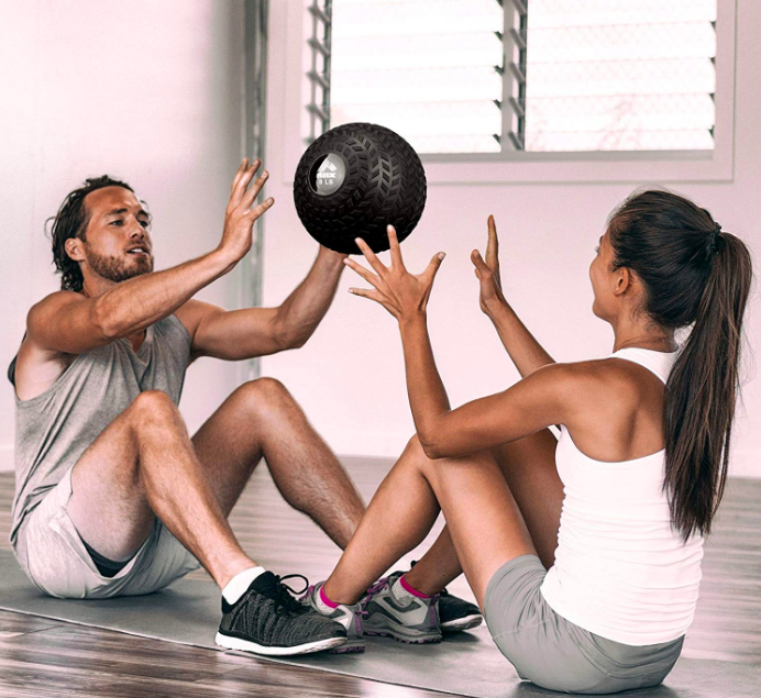 Two people sitting on the floor throwing a medicine ball to each other