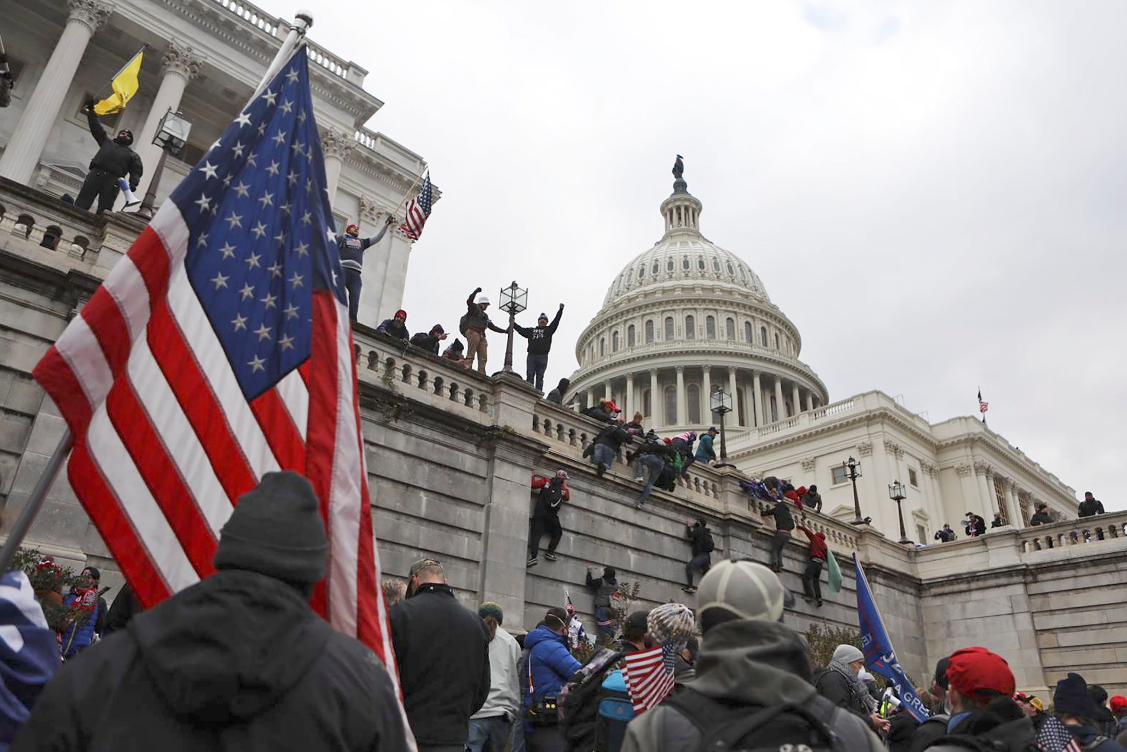 People scale the walls outside the Capitol building in DC