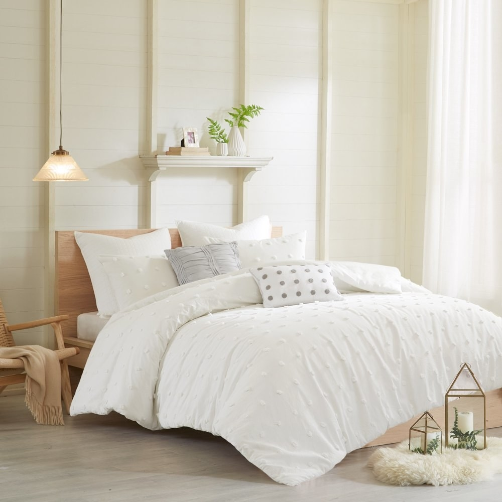 a white cotton duvet cover set with two pillow. on the set there is a geometric polka dot design
