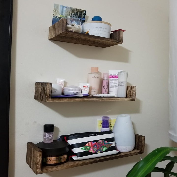 reviewer photo showing three shelves used for makeup products