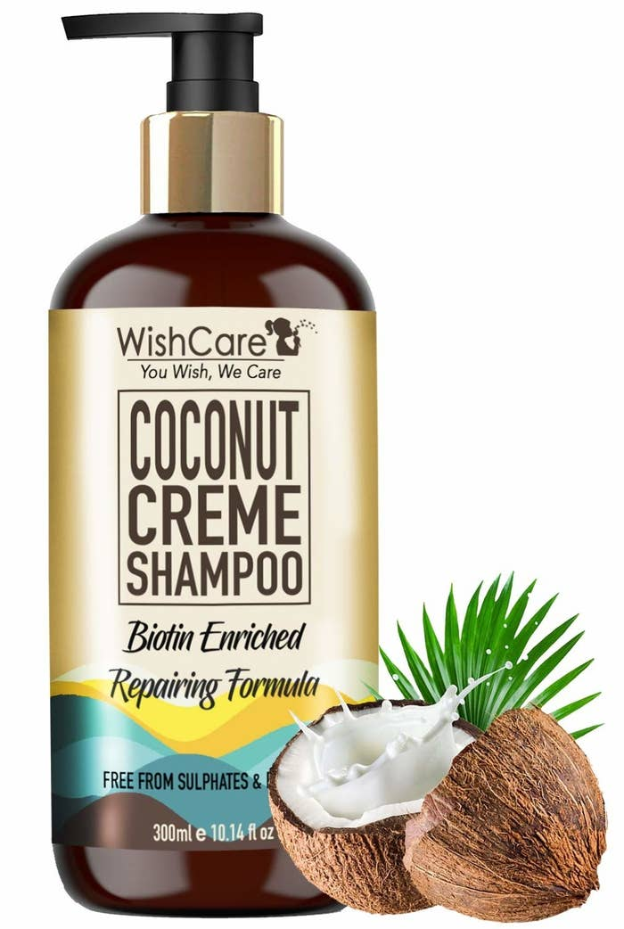 Packaging of the coconut creme shampoo next to coconuts