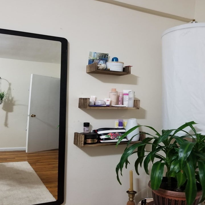 same reviewer showing three shelves used for makeup products from farther away