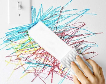 Someone using the sponge to erase crayon on a wall