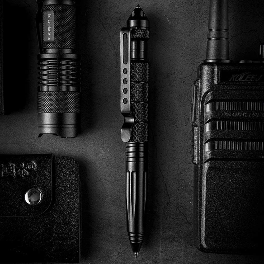 A flatlay of the tactical pen next to a mini flashlight