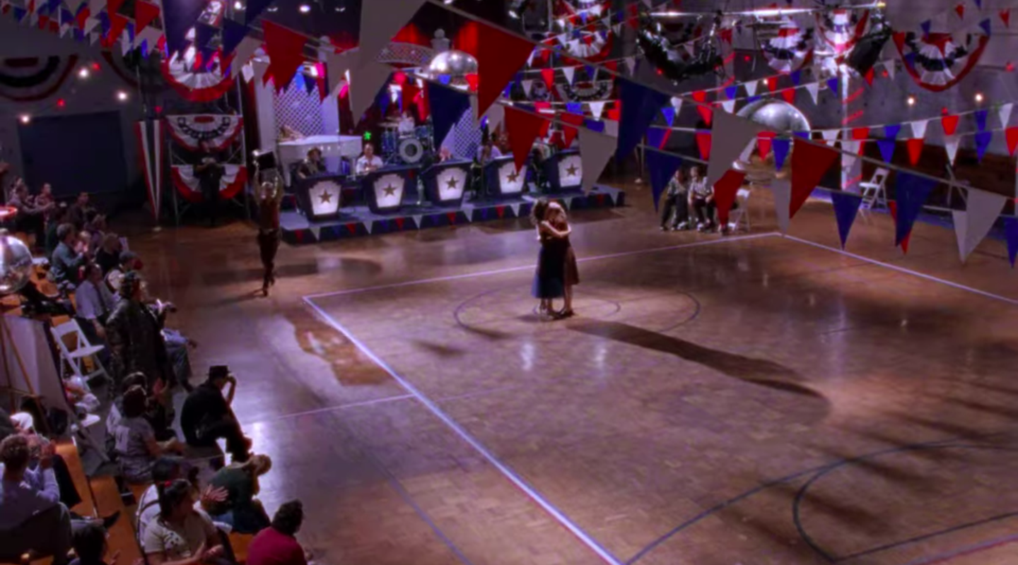 Rory and Lorelai hugging as Kirk dances around the gym with the trophy