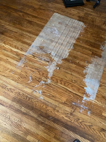 A reviewer's photo of their first attempt to removed sticky residue from their hardwood floor using the formula
