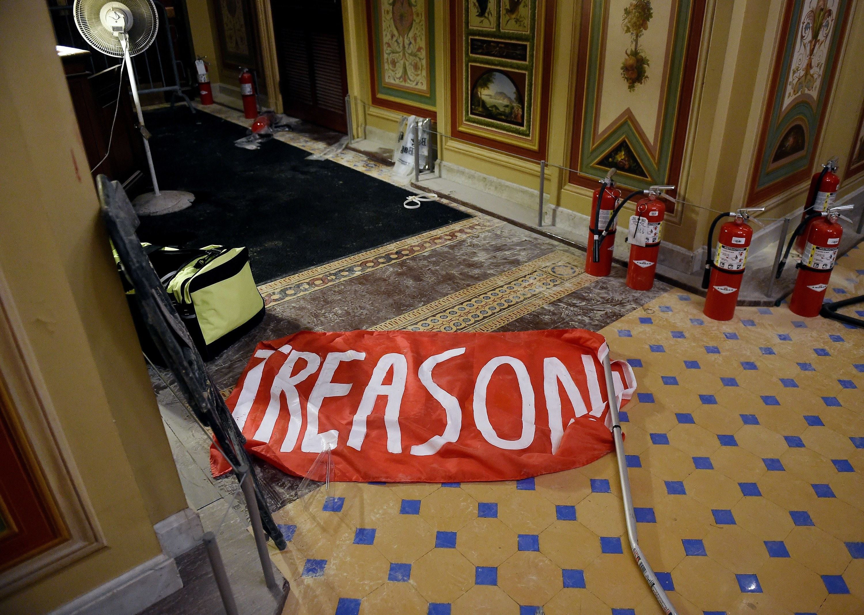 "Fire extinguishers and a red flag with ""treason"" written on it lie in a hallway"