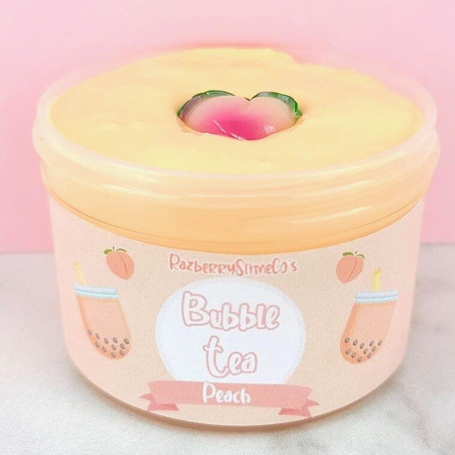 A peach colored jar of bubble tea slime with a peach charm on top