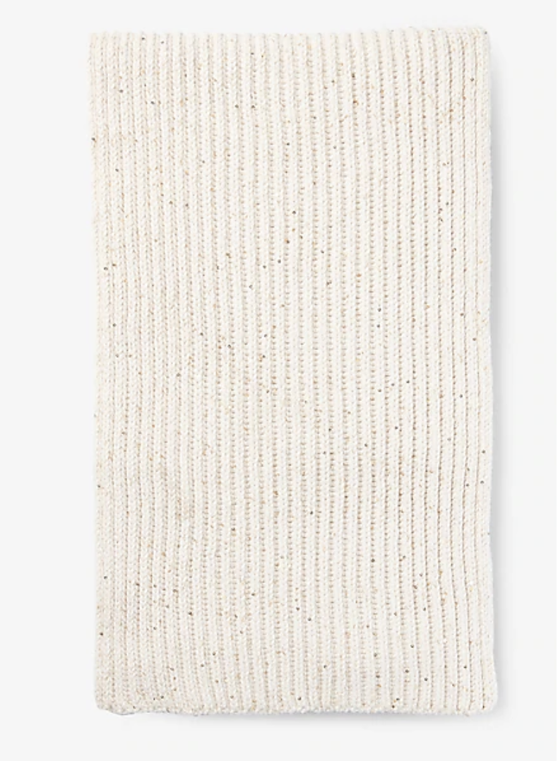 An ivory knit scarf with tiny sequins stitched into it