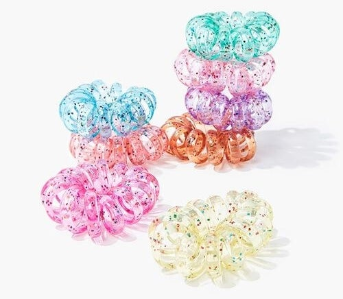 spiraled plastic hairties in clear, pink, orange, purple, and blue with multicolored glitter