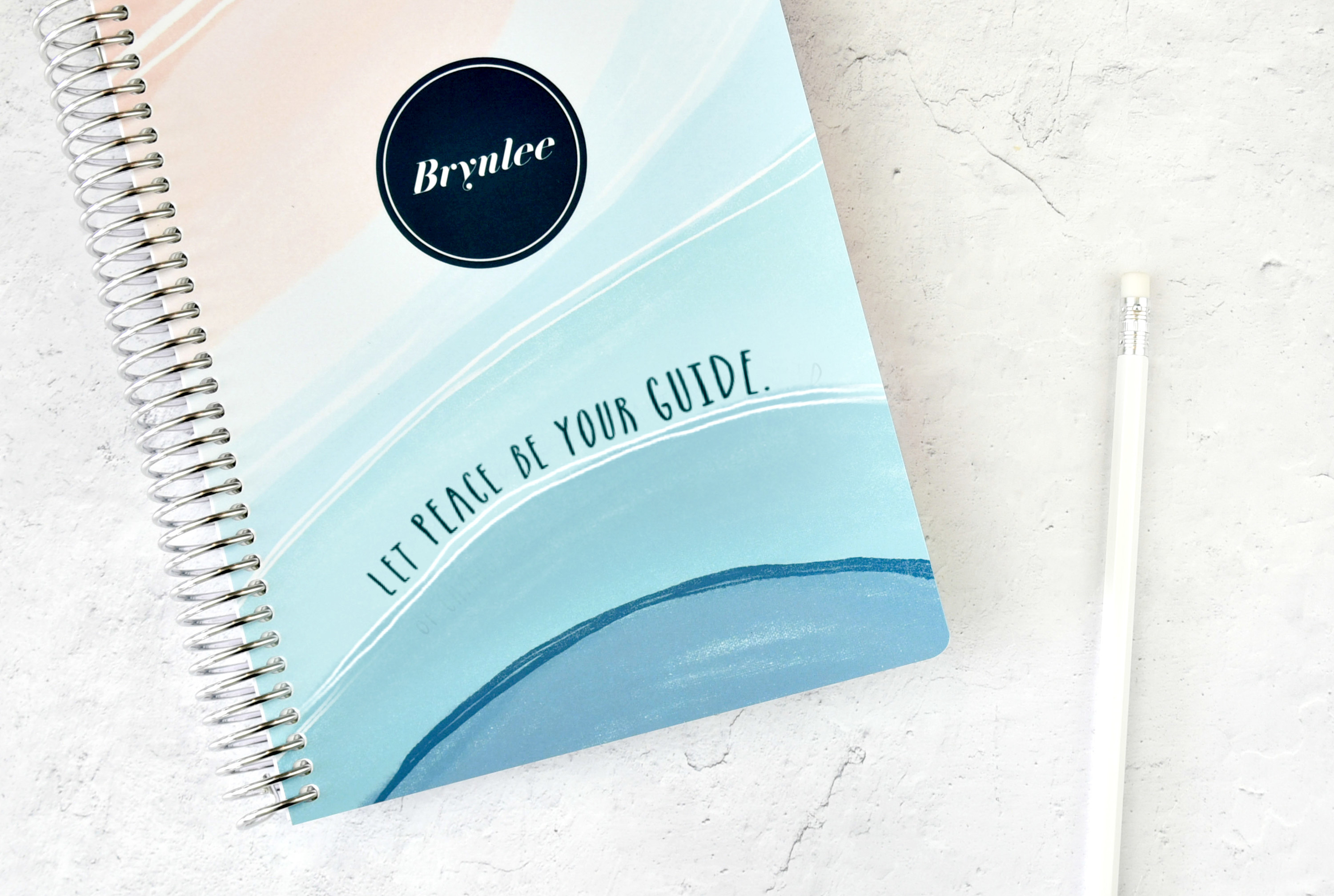 """A coiled planner with a badge that says """"Brynlee"""" and """"Let peace be your guide"""" sitting next to a pencil"""