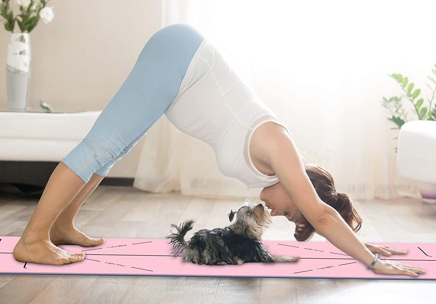 A person doing downward dog with their dog