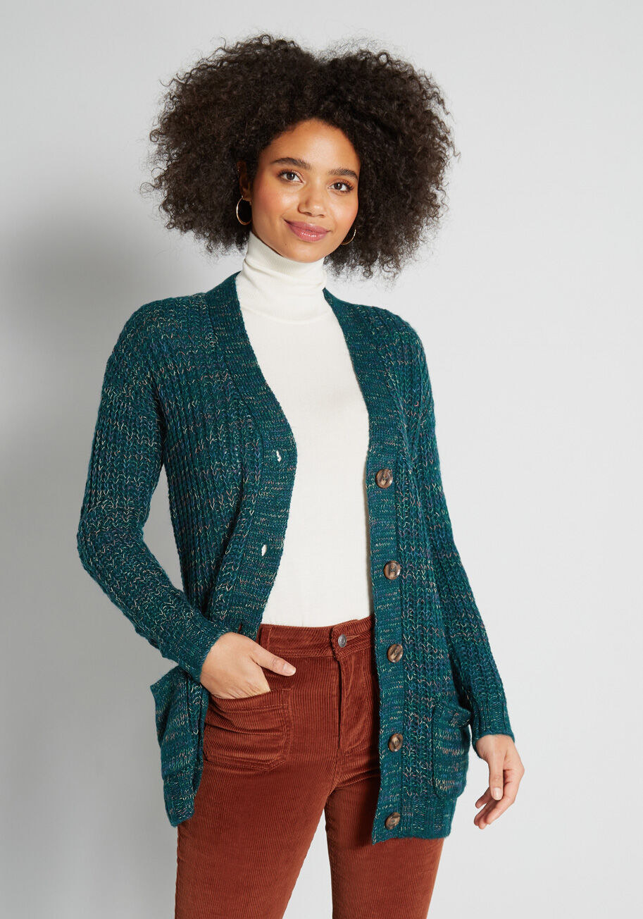 Model in the teal cardigan with burgundy corduroy pants