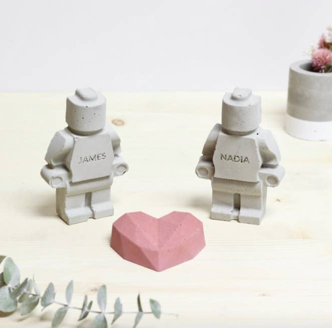 A pair of concrete Lego-shaped people next to a concrete heart