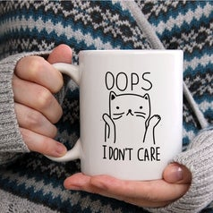 """a model holding a white mug with a cat on it and the words """"oops I don't care"""""""