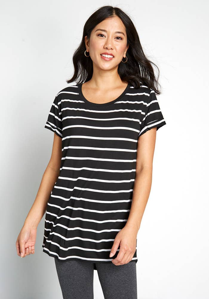 Model in the black and white striped tunic with gray leggings