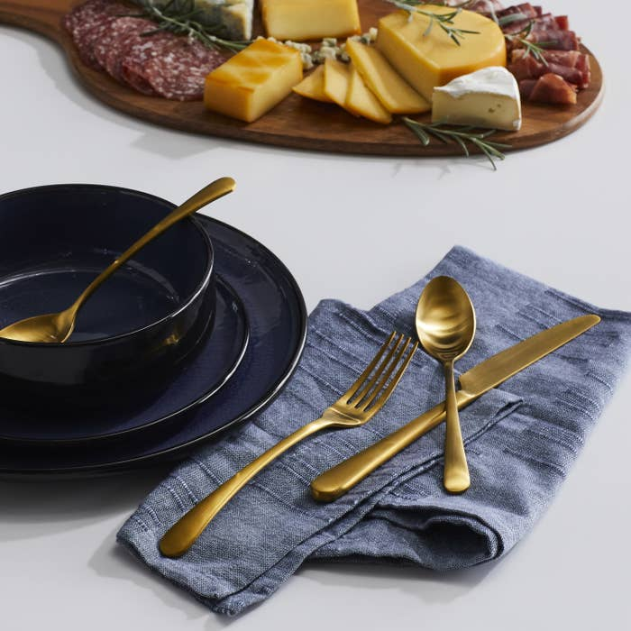 gold flatware on a cloth napkin and a blue dish