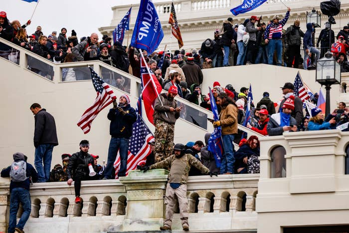 Rioters on the steps of the U.S. Capitol waving U.S. and Trump flags