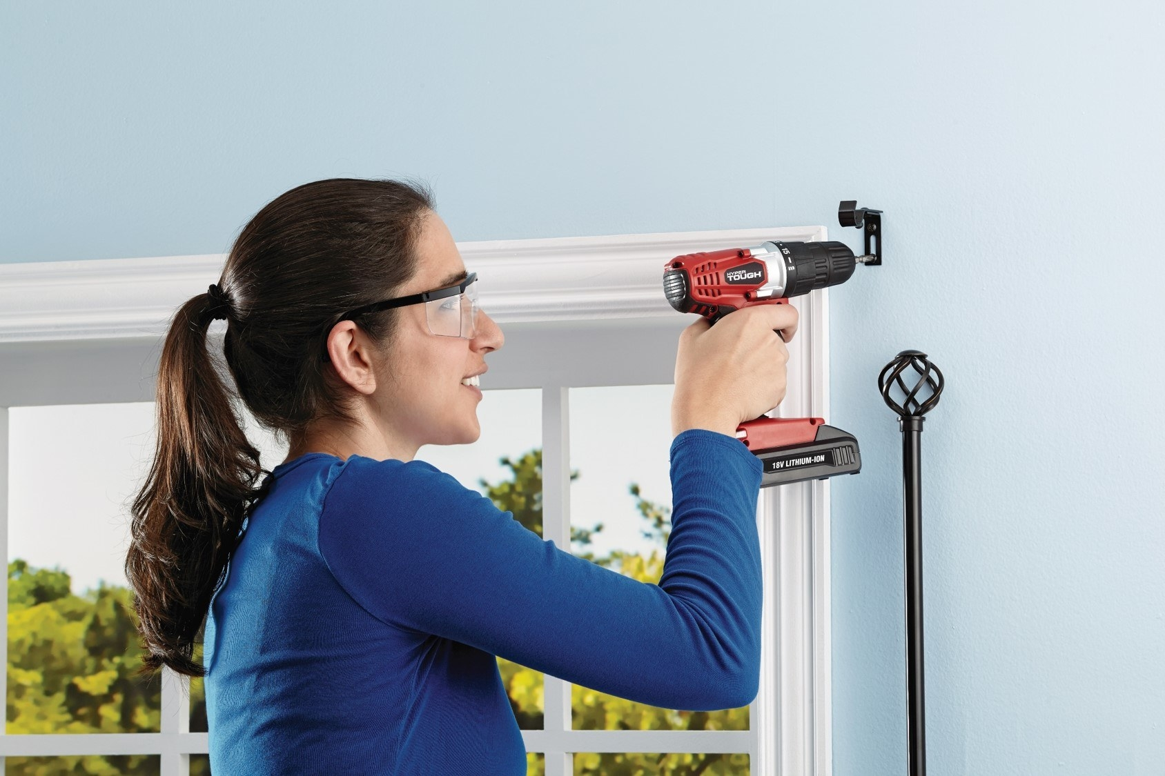 person using a red power drill to drill a curtain rod holder into the wall