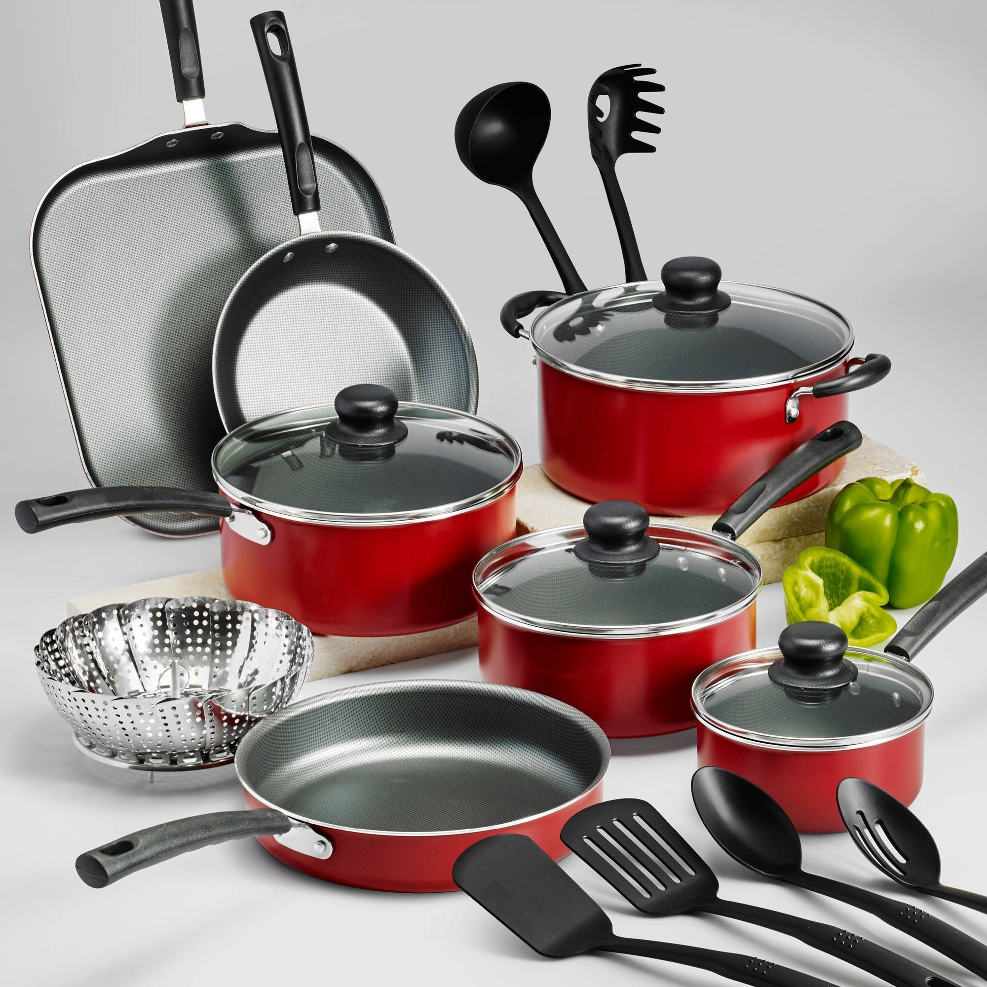 a set of red cookware and black cooking utensils