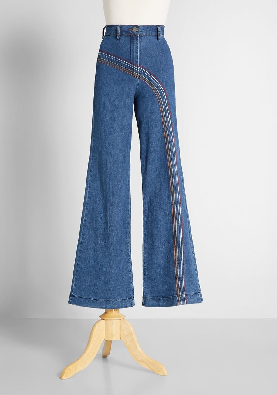 Mid-wash jeans with rainbow embroidery on a white mannequin