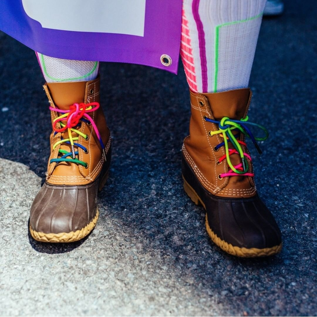 A model wearing the boots with rainbow-colored laces