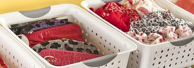 The plastic storage baskets being used to organized miscellaneous items in a closet.