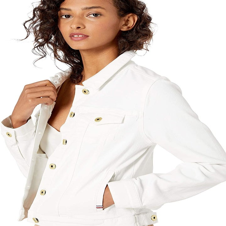 Front view of a model wearing the coat in white