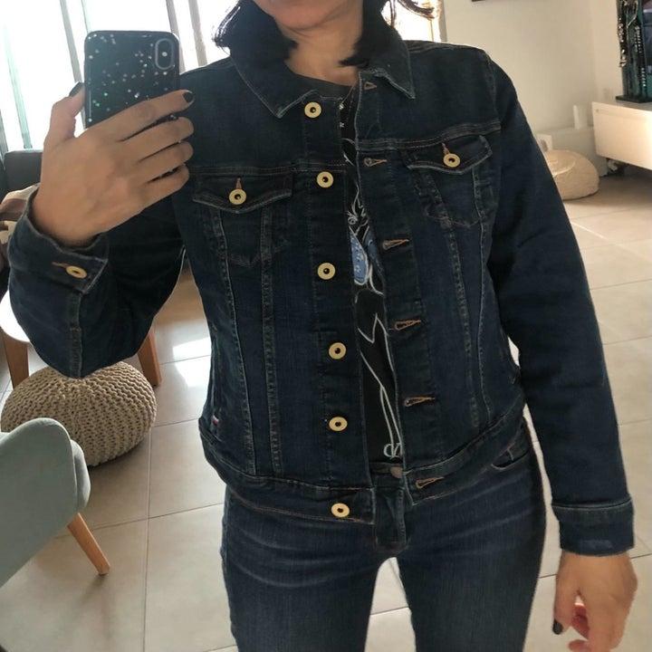 A reviewer wearing the dark denim jacket