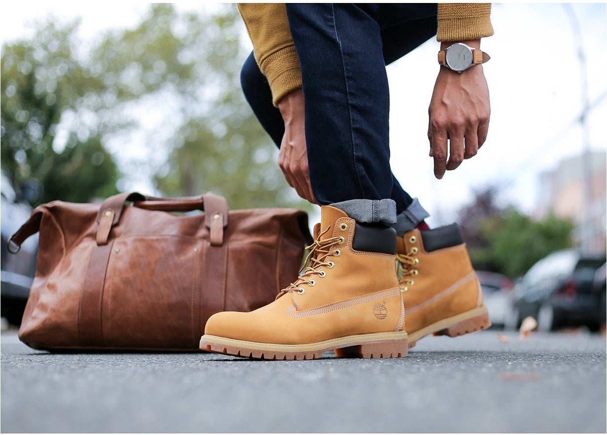 Model wearing a pair of Timberlands in wheat
