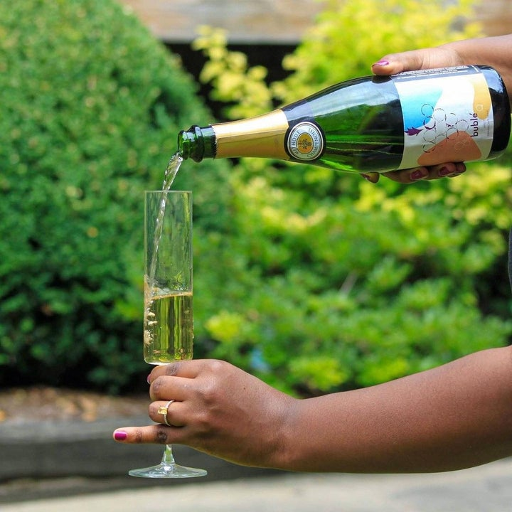 Model's hand holding a champagne flute with their pinky sticking out (yes, fancy!) as they pour the champagne into it
