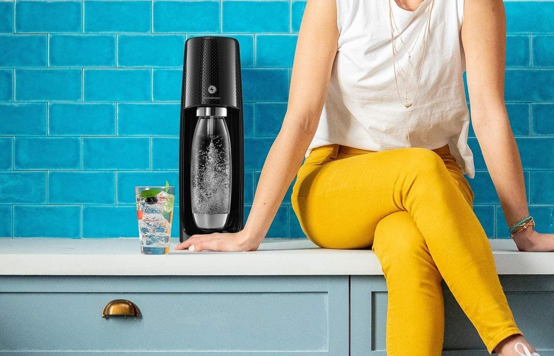 Model sitting next to the SodaStream machine in black