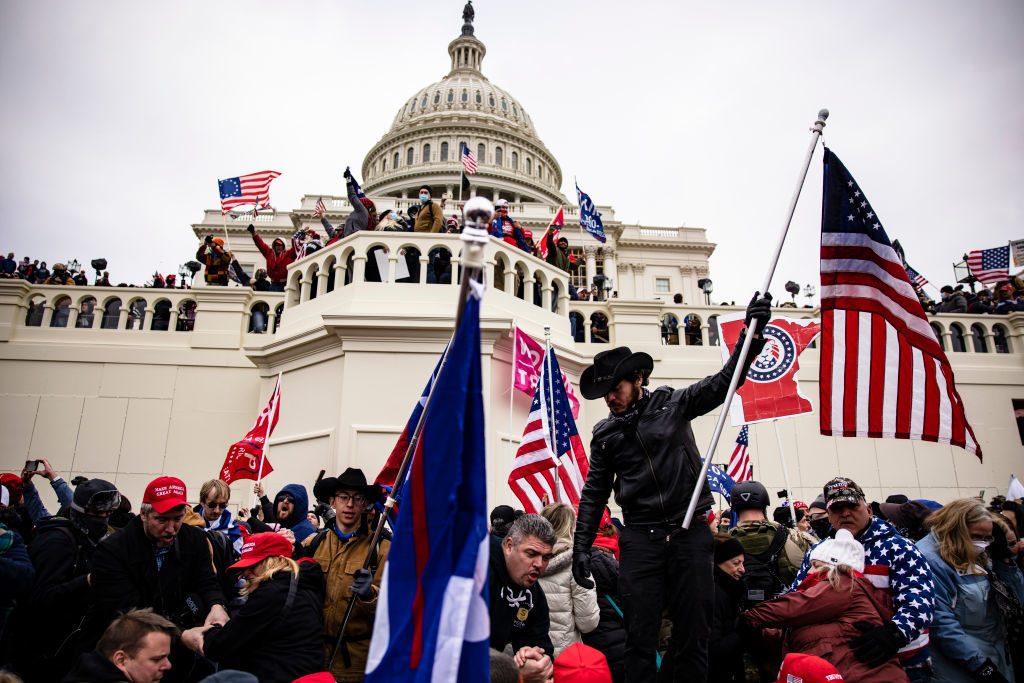 Rioters on the steps of the Capitol waving U.S. flags