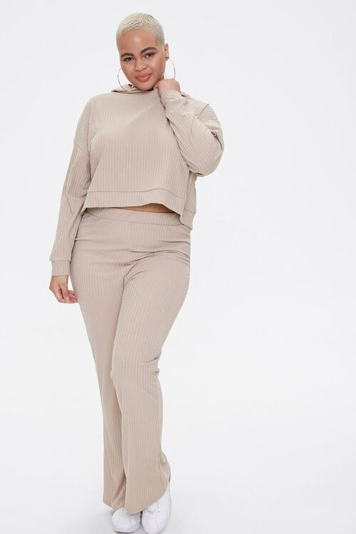 Model wearing the cropped hoodie and flare pants in a ribbed fabric in taupe