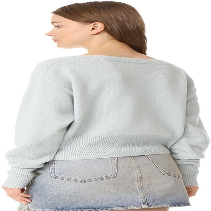 Back view of a model wearing the sweater in light winter green