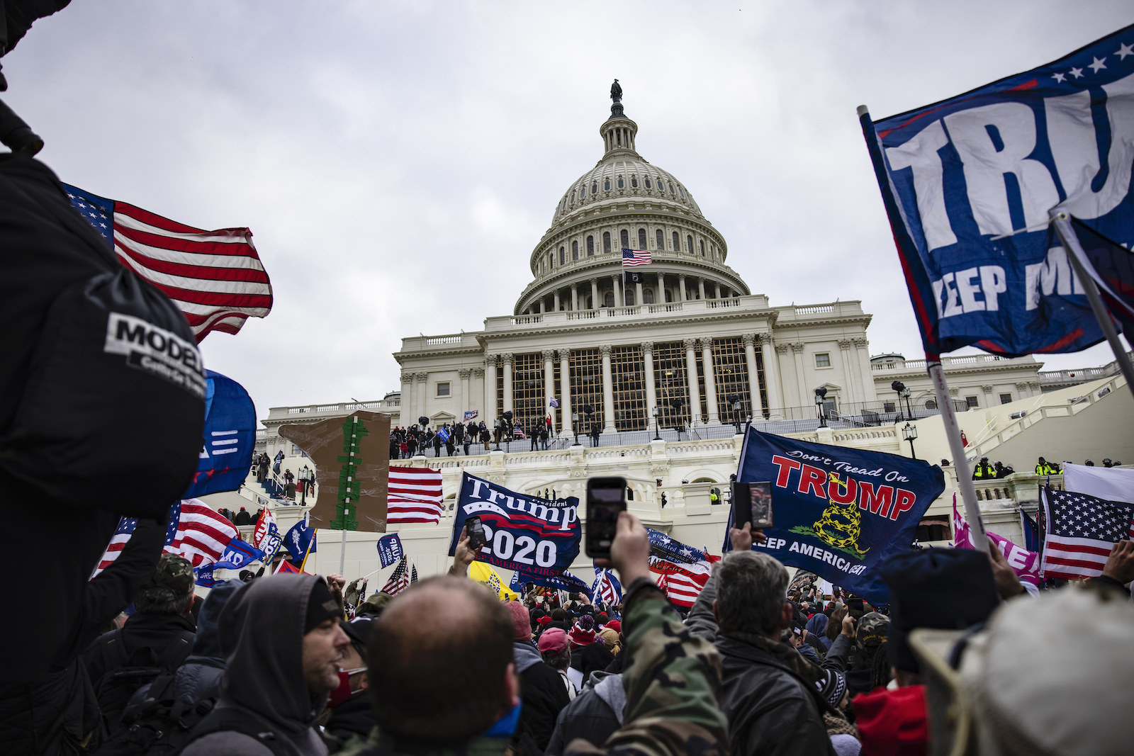 "A crowd of people carry flags that say ""Trump 2020,"" ""Don't Tread on Me,"" and ""Keep America Great,"" among other signs outside the steps of the US Capitol building"