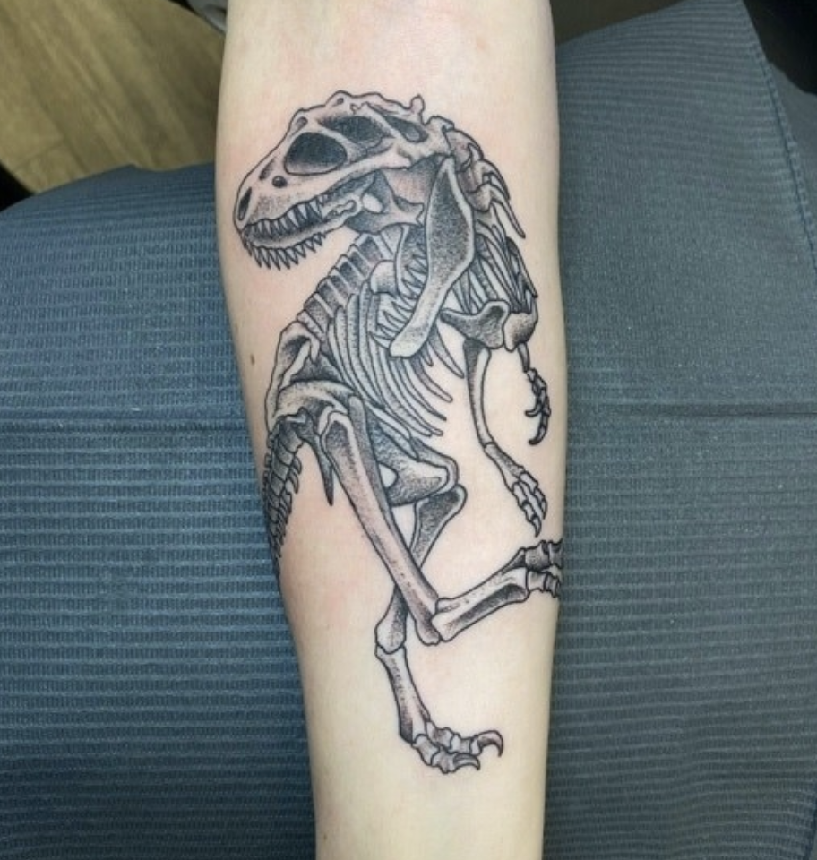 An arm tattoo of a T-Rex's bones